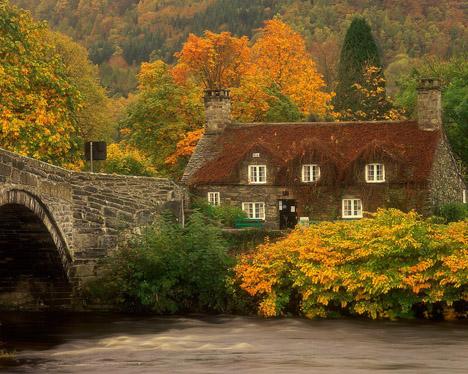 Старый каменный дом и мост в осенних